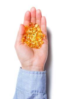 Ręka trzyma kapsułki omega-3 na białym tle. tabletki oleju rybnego na dłoni