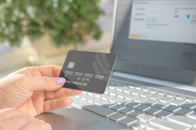 Ręka trzyma kartę kredytową i za pomocą laptopa. zakupy online, e-commerce, bankowość internetowa