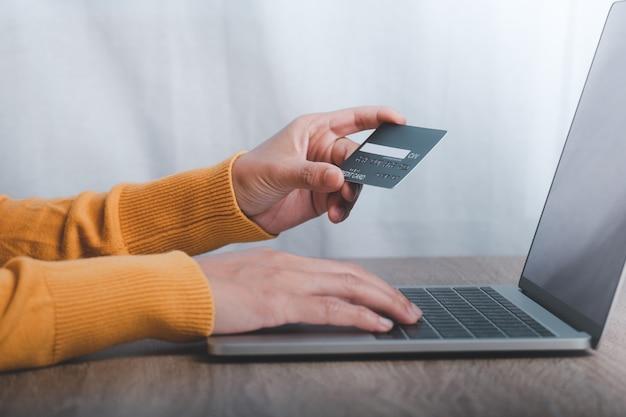 Ręka trzyma kartę kredytową i za pomocą laptopa.