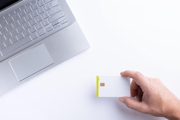 Ręka trzyma kartę kredytową podczas płacenia online z laptopem. widok z góry z miejsca kopiowania.