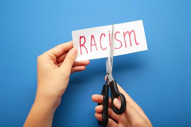 Ręka trzyma kartę z rasizmem tekst. widok z góry czarnych nożyczek do cięcia karty papieru z rasizmem słowa na niebieskim tle.