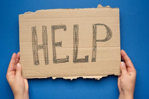 Ręka trzyma kawałek kartonu z napisem pomoc