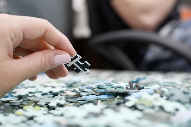 Ręka trzyma kawałek stosu puzzli.