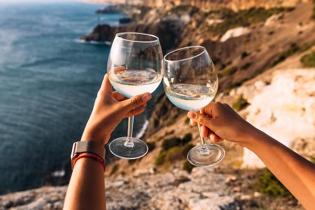 Ręka trzyma kieliszek wina nad morzem. podbródek. romantyczne wakacje. dwie ręce trzymając kieliszki do wina na tle morza. skopiuj miejsce