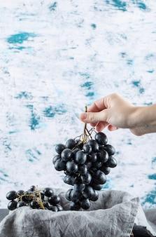 Ręka trzyma kilka ciemnych świeżych winogron.