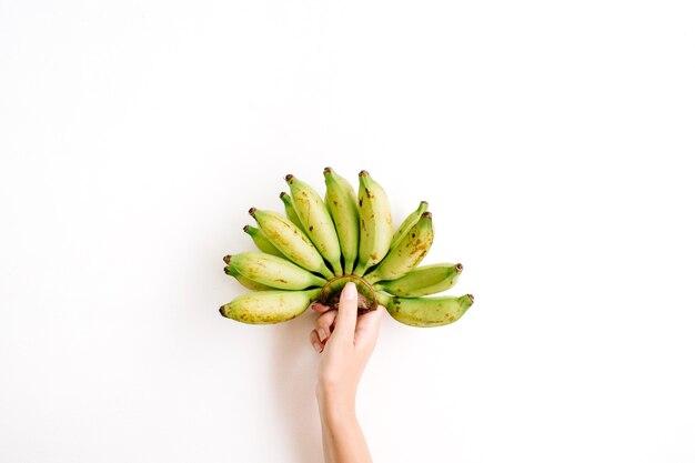 Ręka trzyma kiść bananów na białym tle