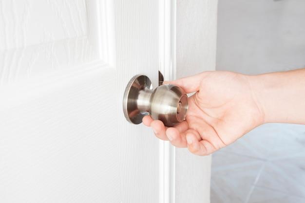 Ręka trzyma klamkę na białych drzwiach