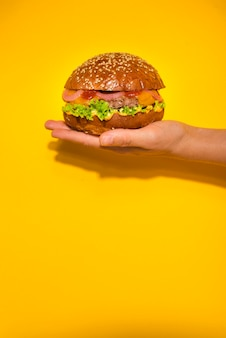 Ręka trzyma klasyczny burger wołowy z sałatą