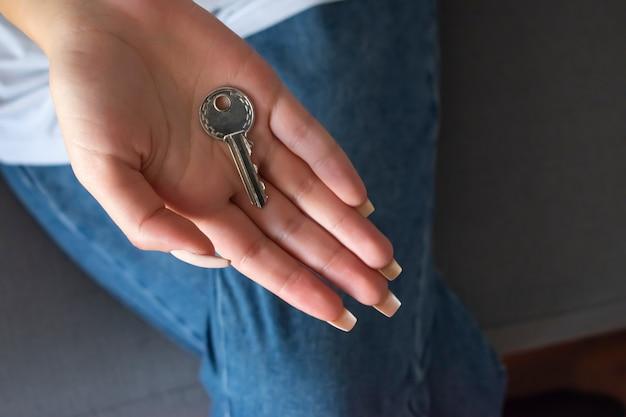 Ręka trzyma klucz do domu, agent nieruchomości.