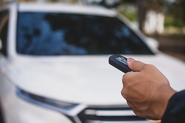 Ręka trzyma klucz samochodowy, aby otworzyć samochód