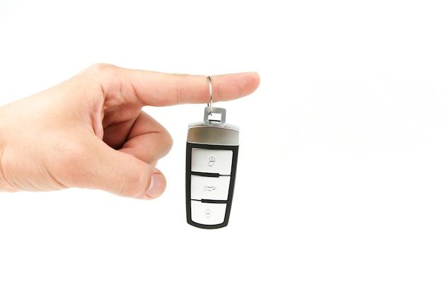 Ręka trzyma kluczyk samochodowy na białym tle