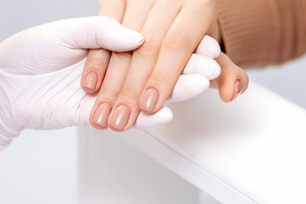 Ręka trzyma kobiece palce z beżowym manicure