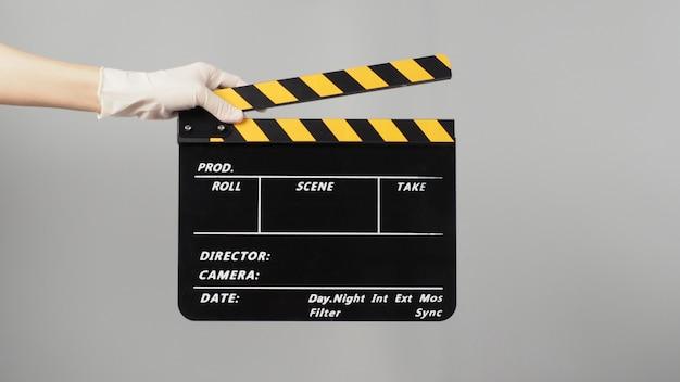 Ręka trzyma kolor żółty z czarną klapą i nosi białą rękawicę medyczną. jest używana w produkcji wideo i przemyśle filmowym na szarym tle.