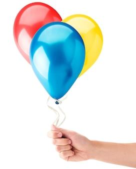 Ręka trzyma kolorowe balony w kolorze czerwonym, niebieskim i żółtym na białym tle