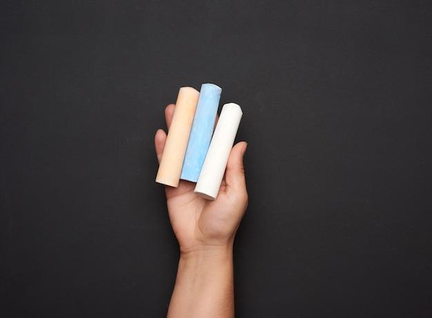 Ręka trzyma kolorowe kawałki kredy