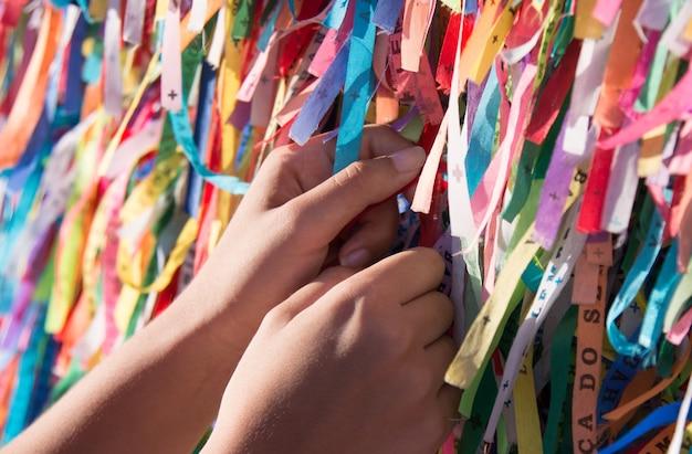 Ręka trzyma kolorowe wstążki w siatce kościoła senhor do bonfim.