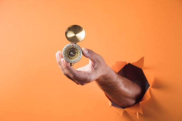 Ręka trzyma kompas na pomarańczowym tle