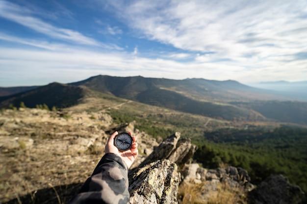 Ręka trzyma kompas na szczycie góry, pojęcie podróżowania.