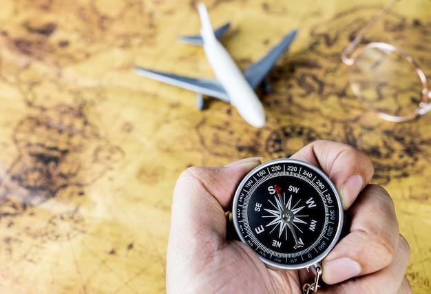 Ręka trzyma kompas na vintage samolotem podróży lotniczych