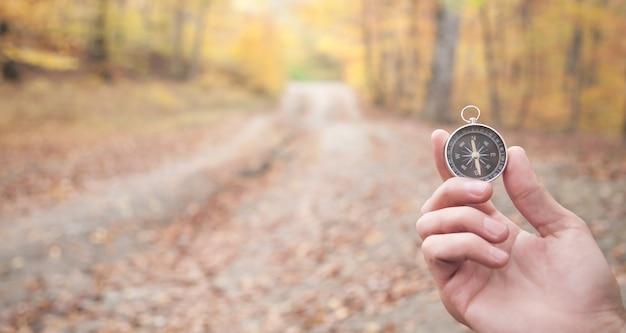 Ręka trzyma kompas w lesie jesienią