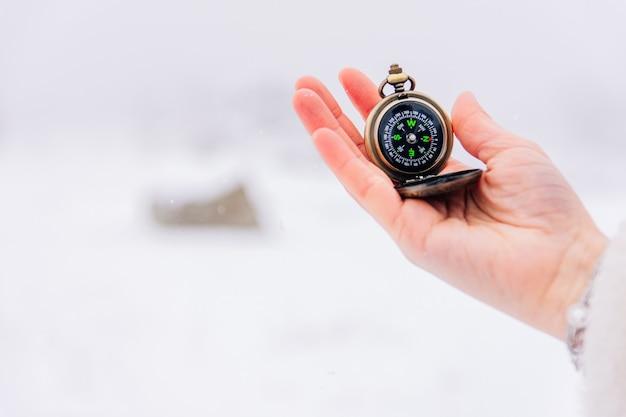 Ręka trzyma kompas w śniegu