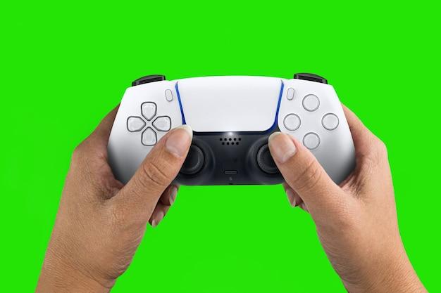 Ręka trzyma kontroler gier nowej generacji biały na białym tle na tle zielonego ekranu. klucz chroma.