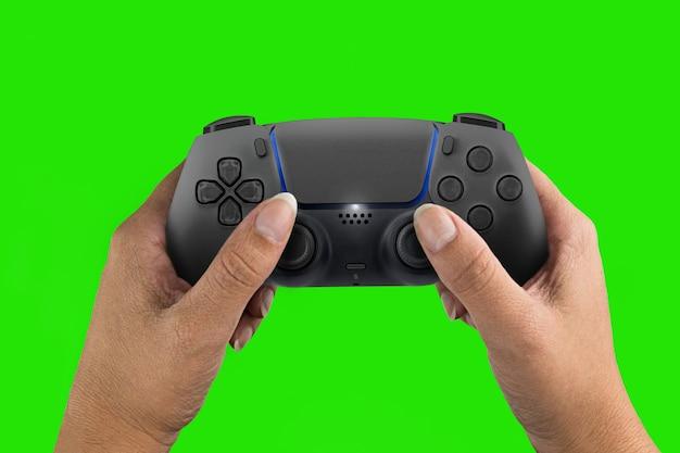 Ręka trzyma kontroler gier nowej generacji czarny na białym tle na tle zielonego ekranu. klucz chroma.