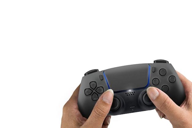 Ręka trzyma kontroler gier nowej generacji czarny na białym tle.