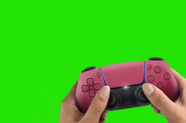 Ręka trzyma kontroler gier nowej generacji czerwony na białym tle na tle zielonego ekranu. klucz chroma.
