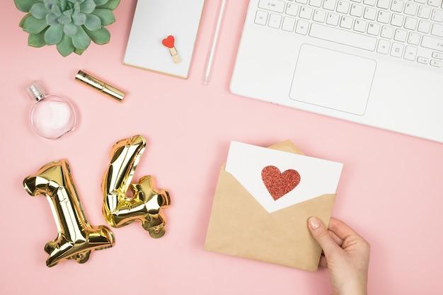 Ręka trzyma kopertę miłości na różowym pastelowym stole z innymi dostawami