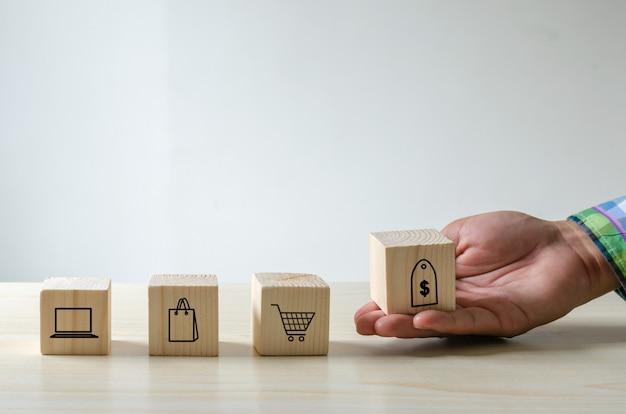 Ręka trzyma kostki zakupy ikony. koncepcja biznesowa