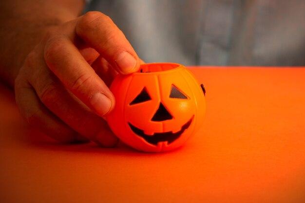 Ręka trzyma kosz cukierków halloween dyni. skopiuj miejsce. selektywne skupienie.