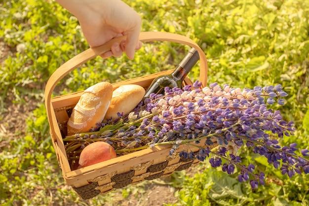 Ręka trzyma kosz z kwiatami, jedzeniem, winem, owocami na lato, słoneczne tło