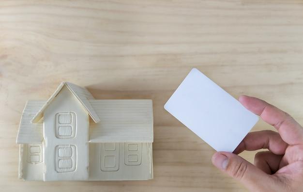 Ręka trzyma kredytową kartę i dom na drewnianym tle.