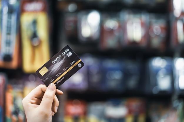 Ręka trzyma kredytową kartę z plamy supermarketem, zakupy i handlu detalicznego concep