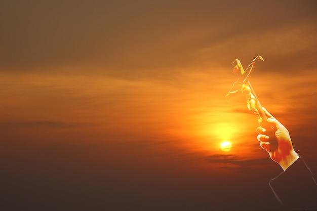 Ręka trzyma krzyż jezusa z wschodem słońca wielokolorowe niebo abstrakcyjne tło natury