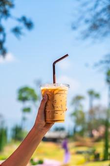 Ręka trzyma kubek mrożonej kawy latte