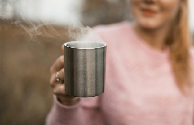 Ręka trzyma kubek z gorącym napojem na zewnątrz