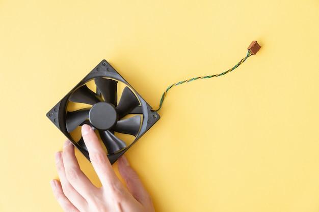 Ręka trzyma laptopu op pc fan na żółtym tle z kopii przestrzenią
