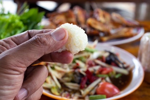 Ręka trzyma lepki ryż z sałatką z papai