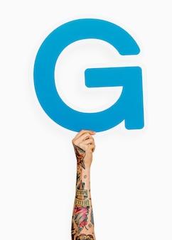 Ręka trzyma literę g