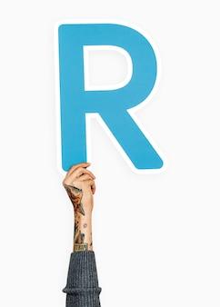 Ręka trzyma literę r znak