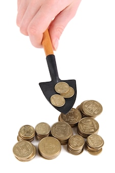 Ręka trzyma łopatę z monetami na białym tle