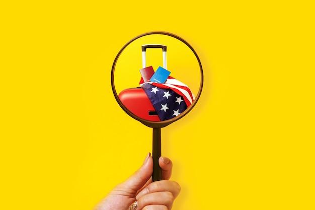 Ręka trzyma lupę i patrzy na amerykańską flagę i walizkę z paszportami
