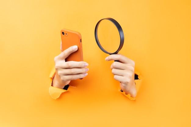 Ręka trzyma lupę i telefon wystający ze ściany