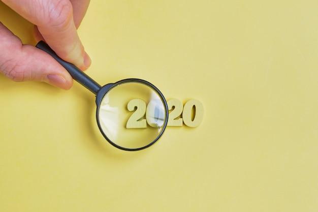 Ręka trzyma lupę nad abstrakcyjnym rokiem 2020 cyfr drewnianych na żółtym tle.