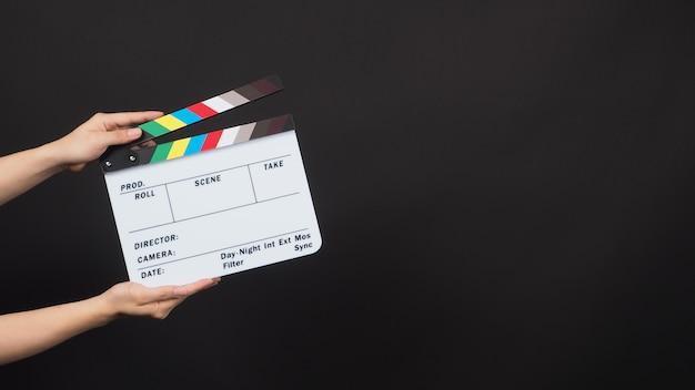 Ręka trzyma łupek filmowy. jest używany w produkcji wideo i przemyśle filmowym na czarnym tle.