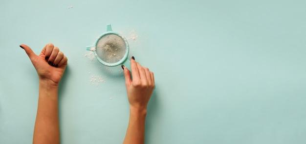 Ręka trzyma mąkę sito na niebieskim tle.