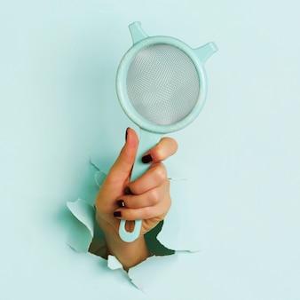 Ręka trzyma mąkę sito przez otwór na niebieskim tle.