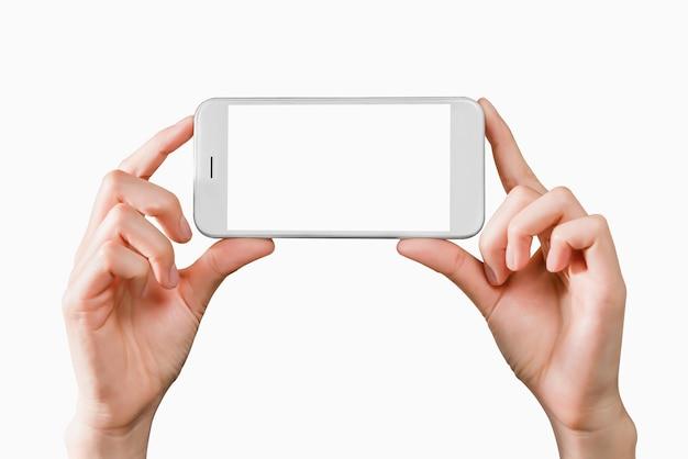 Ręka trzyma makieta smartfona z pustym ekranem na na białym tle